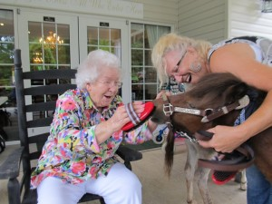 Kathy Ivy and Cole with a smiling resident of Cameron Hall Assisted Living